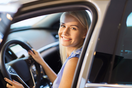 car driving: auto business, car sale, consumerism , transportation and people concept - happy woman sitting in or driving car