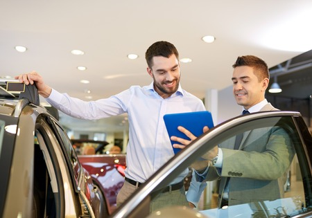 sales representative: auto business, car sale, technology and people concept - happy man and car dealer with tablet pc computer in auto show or salon