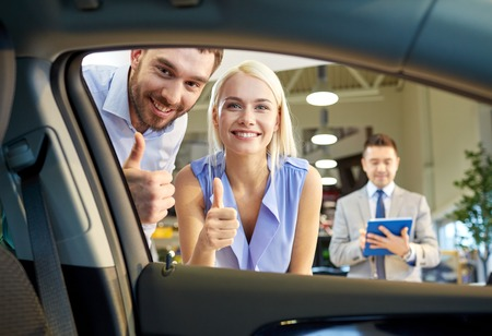 자동차 사업, 자동차 판매, 기술과 사람들 개념 - 오토 쇼 또는 살롱에서 자동차 딜러와 함께 행복한 커플 스톡 콘텐츠