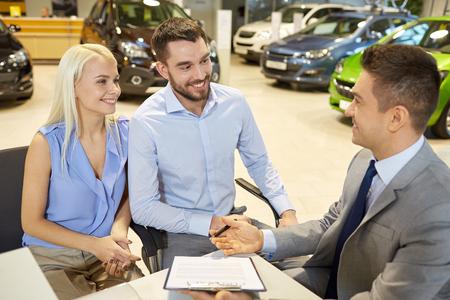 Negocio de los automóviles, la venta y la gente concepto - feliz pareja con distribuidor de comprar coche en salón del automóvil o el salón Foto de archivo - 37056042