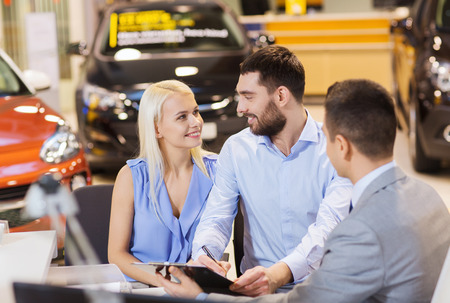 car loan: auto business, sale and people concept - happy couple with dealer buying car in auto show or salon