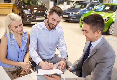 car rent: auto business, sale and people concept - happy couple with dealer buying car and signing documents in auto show or salon
