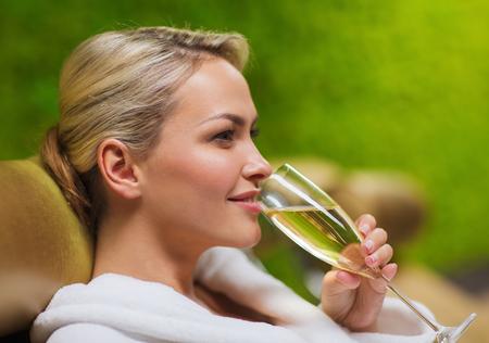 jovenes tomando alcohol: personas, belleza, estilo de vida, las vacaciones y el concepto de relajación - hermosa mujer joven en traje de baño blanco acostado en chaise-longue y bebiendo champán en el spa