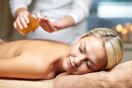 massage: gens, beaut�, spa, mode de vie sain et de d�tente notion - close up de la belle jeune femme allong�e les yeux ferm�s sur table de massage et th�rapeute, tenue, bouteille d'huile dans le spa Banque d'images