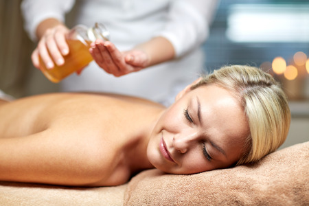 massage oil: people, beauty, spa, healthy lifestyle and relaxation concept - close up of beautiful young woman lying with closed eyes on massage table and therapist holding oil bottle in spa