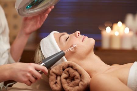masajes faciales: personas, belleza, spa, cosmetología y tecnología concepto - cerca de la hermosa mujer joven tendido con los ojos cerrados que tiene la cara de masaje por el masajeador en spa Foto de archivo