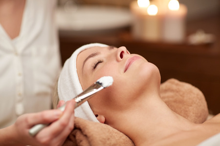 people, beauty, spa, cosmetology and skincare concept - close up of beautiful young woman lying with closed eyes and cosmetologist applying facial mask by brush in spa Imagens - 37055906