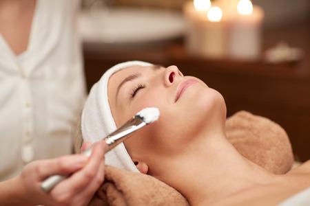 limpieza de cutis: personas, belleza, spa, cosmetolog�a y cuidado de la piel concepto - cerca de la hermosa mujer joven tendido con los ojos cerrados y cosmet�loga que aplican la m�scara facial con brocha en el spa