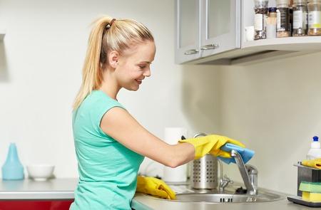 Las personas, el trabajo doméstico y el concepto de servicio de limpieza - mujer feliz en guantes de limpieza del grifo con un trapo en la cocina de su casa Foto de archivo - 37055911