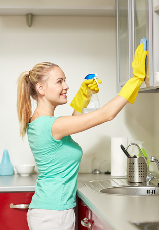 spray bottle: people, housework and housekeeping concept - happy woman in protective gloves cleaning cabinet with rag and cleanser at home kitchen