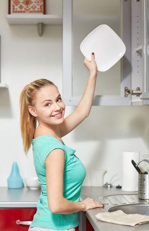 storing: people, housework and housekeeping concept - happy woman putting plate to kitchen cabinet Stock Photo