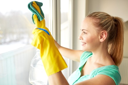 sprays: people, housework and housekeeping concept - happy woman in gloves cleaning window with rag and cleanser spray at home Stock Photo