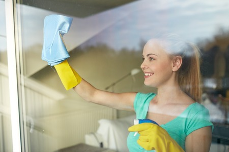 work glove: people, housework and housekeeping concept - happy woman in gloves cleaning window with rag and cleanser spray at home Stock Photo