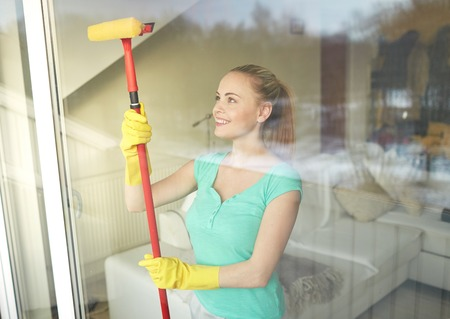 clean window: people, housework and housekeeping concept - happy woman in gloves cleaning window with sponge mop at home Stock Photo
