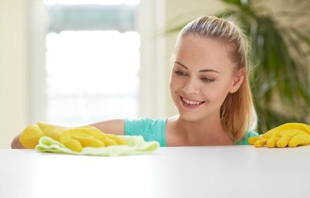 人々 は、家事やコンセプト - 幸せな女家庭の台所でテーブルを洗浄の家事