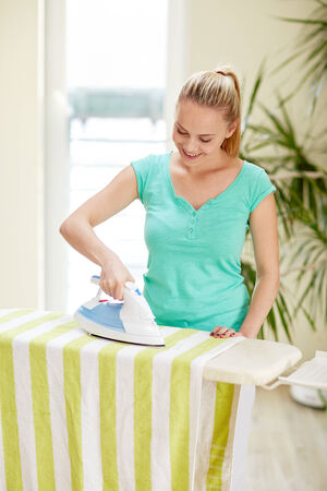 the iron lady: people, housework, laundry and housekeeping concept - happy woman with iron and ironing board at home