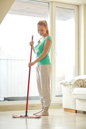mopping: people, housework and housekeeping concept - happy woman with mop cleaning floor at home