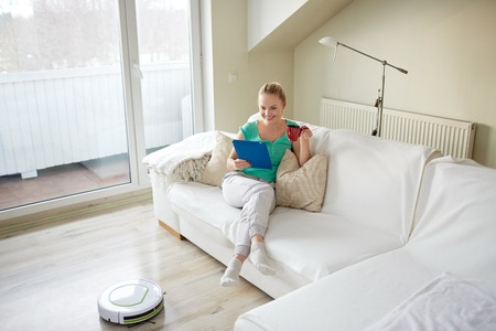 vacuuming: people, housework and technology concept - happy woman with tablet pc computer and robot vacuum cleaner drinking tea at home Stock Photo