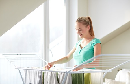 hanging woman: people, housework, laundry and housekeeping concept - happy woman hanging clothes on dryer at home