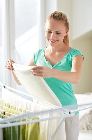 ropa colgada: las personas, el trabajo doméstico, lavandería y servicio de limpieza concepto - mujer feliz colgar la ropa en la secadora en casa