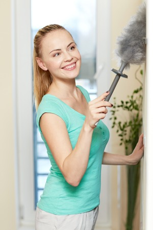 people, housework and housekeeping concept - happy woman with duster cleaning at home 版權商用圖片