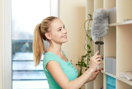 orden y limpieza: las personas, el trabajo dom�stico y el concepto de servicio de limpieza - mujer feliz con la limpieza plumero en casa Foto de archivo