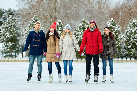 ice skating: people, winter, friendship, sport and leisure concept - happy friends ice skating on rink outdoors Stock Photo