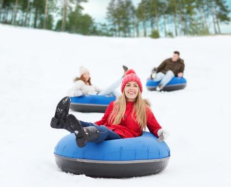 hombres jovenes: invierno, el ocio, el deporte, la amistad y el concepto de la gente - grupo de amigos felices deslizarse sobre los tubos de nieve