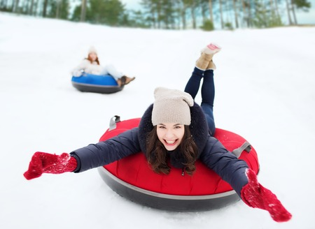 having fun in the snow: winter, leisure, sport, friendship and people concept - group of happy friends sliding down on snow tubes