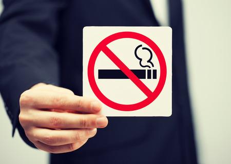 禁煙サインを保持していないスーツを着た男の画像