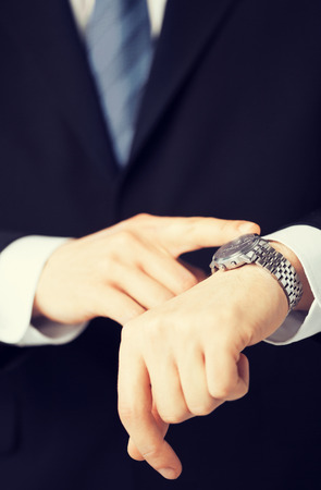 rushing hour: business people and office concept - close up of man looking at wristwatch