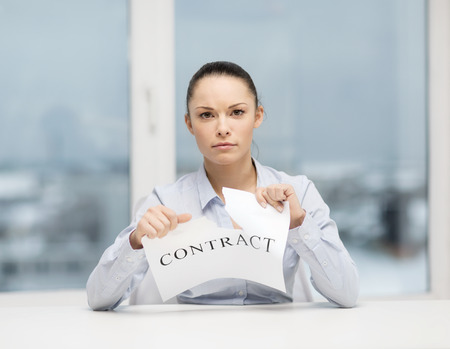 changing form: business, documents, people, legal and real estate concept - serious businesswoman tearing contract Stock Photo