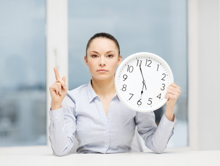 career timing: business, office, school and education concept - attractive businesswoman showing clock with finger up