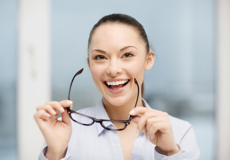 business and education concept - laughing businesswoman with eyeglasses