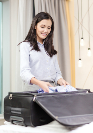 packing suitcase: business, technology, internet and hotel concept - happy businesswoman packing things in suitcase in hotel room Stock Photo