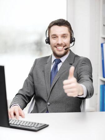 centro de computo: los negocios, la comunicación y la tecnología concepto - Servicio de ayuda masculino con los auriculares y la computadora en centro de atención telefónica que muestra los pulgares para arriba Foto de archivo