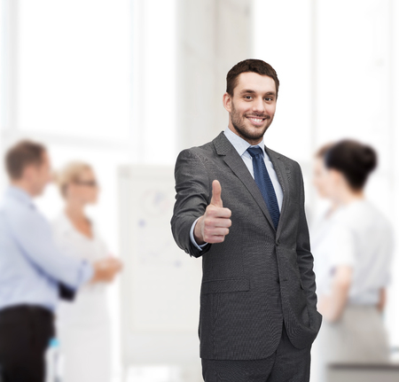 gray suit: business, gesture and office concept - handsome buisnessman showing thumbs up in office
