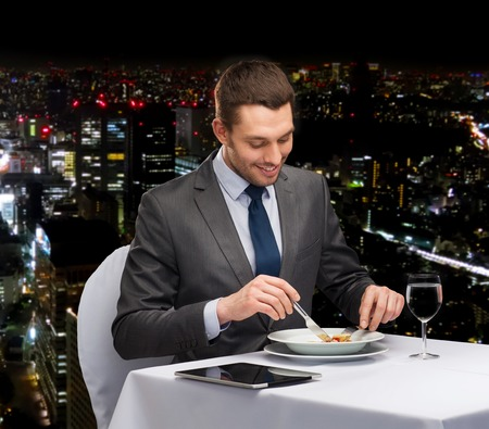 main course: restaurant, people, technology and holiday concept - smiling man with tablet pc eating main course at restaurant Stock Photo