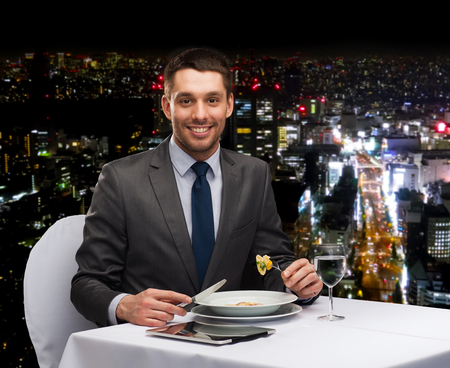 restaurant, people, technology and holiday concept - smiling man with tablet pc eating main course at restaurant Фото со стока