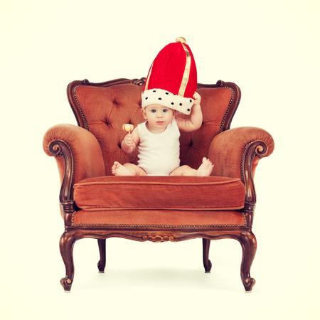 prin: realeza y feliz concepto de niño - adorable bebé real en rey sombrero con el lollipop