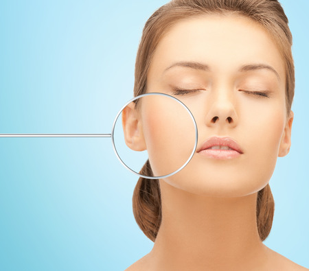 mensen, huidverzorging en schoonheid concept - gezicht van mooie gelukkige jonge vrouw op blauwe achtergrond