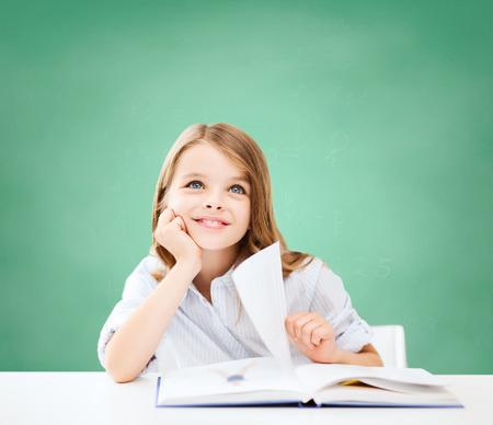 literatura: educaci�n, las personas, los ni�os y la escuela concepto - ni�a estudiante sentado en la mesa con el libro sobre fondo pizarra verde Foto de archivo
