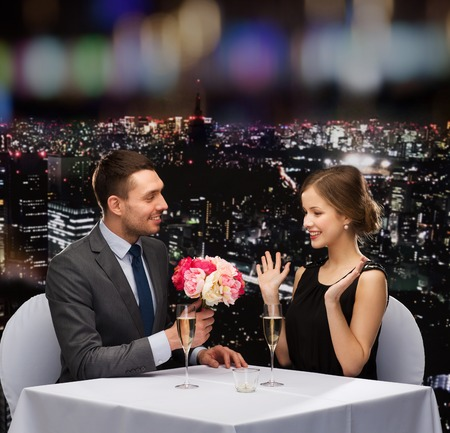 flower bouquet: restaurant, couple and holiday concept - smiling man giving flower bouquet to woman at restaurant