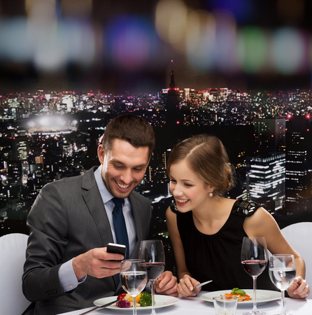 main course: restaurant, technology, couple and holiday concept - smiling couple taking picture of main course with smartphone camera at restaurant