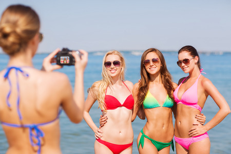 sexy pictures: summer vacation, gesture, travel and people concept - group of smiling young women photographing by camera and waving hands on beach