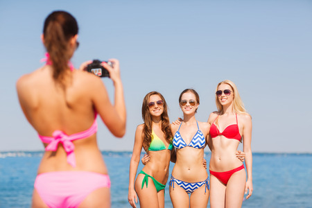 summer vacation bikini: summer vacation, gesture, travel and people concept - group of smiling young women photographing by camera and waving hands on beach