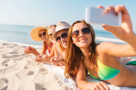 summer vacation, travel, technology and people concept - group of smiling women in sunglasses and hats making selfie with smartphone on beach Stockfoto