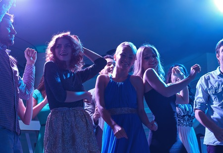 dancing club: party, holidays, celebration, nightlife and people concept - group of happy friends dancing in night club