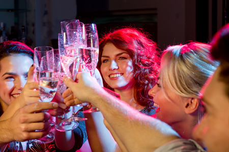 jovenes tomando alcohol: fiesta, días de fiesta, celebración, vida nocturna y la gente conceptuales - amigos sonrientes con copas de champán en el club Foto de archivo