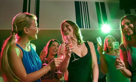 party, holidays, celebration, nightlife and people concept - happy young women with glasses of champagne in club photo
